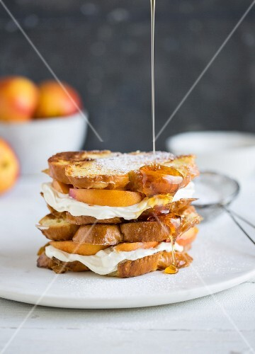 Honey being drizzled over a stack of French toast with cream cheese and apricots