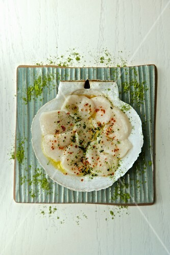 Raw sliced mussels with green tea in a scallop shell