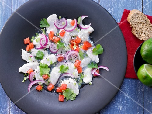 White fish ceviche with red onions and diced tomatoes