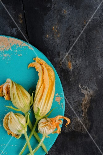 Courgette flowers on a blue wooden board