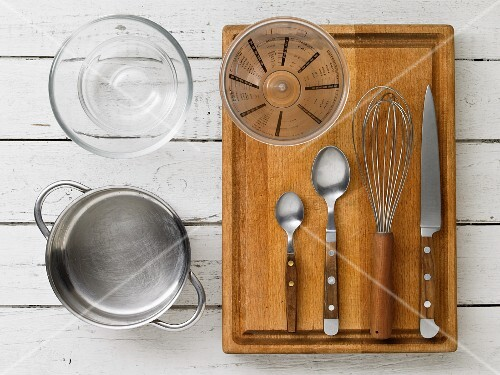 Kitchen utensils: a saucepan, a glass bowl, a measuring cup, cutlery and a whisk
