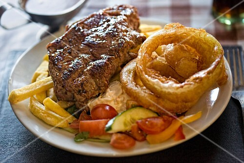 Steak with chips, fried onion rings and salad