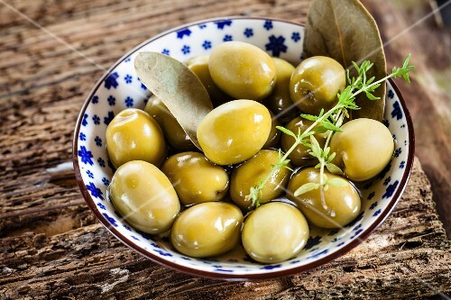 Pickled green olives with a sprig of thyme