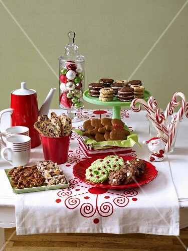 A selection of various Christmas biscuits with candy canes and coffee