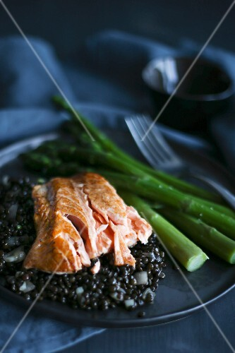 Salmon on a bed of black lentils with green asparagus