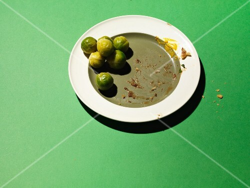 An empty plate with leftover Brussels sprouts