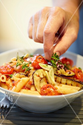 Plating up pasta with grilled aubergine, tomatoes and wild marjoram
