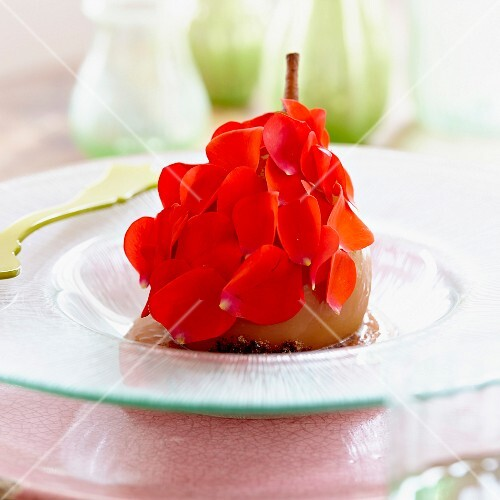 A poached pear with rose petals