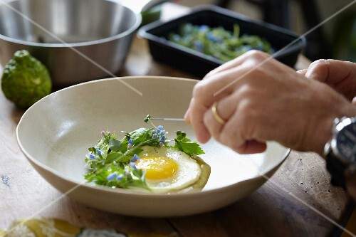 Decorating a fried egg with Blue Ocean cress