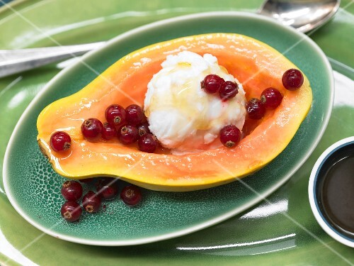 Papaya filled with ice cream and served with redcurrants