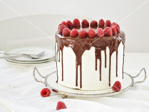 A cake with white chocolate and raspberries