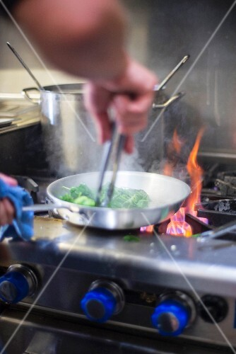 A chef frying vegetables in a pan over the hob