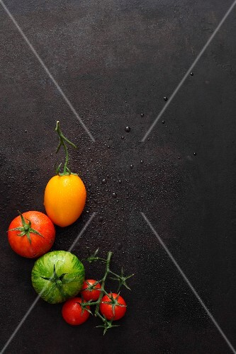 Various tomatoes on a black surface
