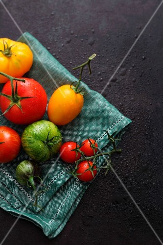Various tomatoes lying on a cloth