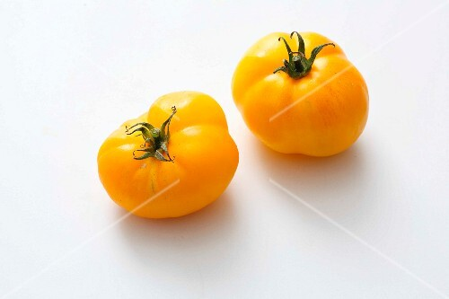 Two yellow beefsteak tomatoes on a white surface