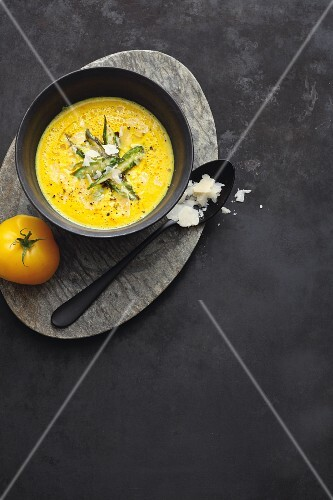 Creamy yellow tomato soup with saffron and green asparagus