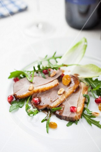 Sliced duck breast with pomegranate seeds and sultanas