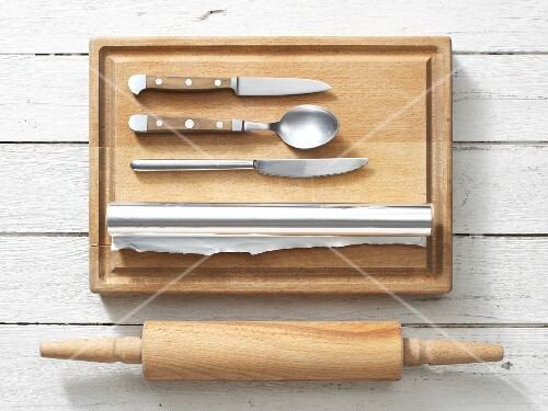 Assorted kitchen utensils: a rolling pin, aluminium foil, knives and a spoon