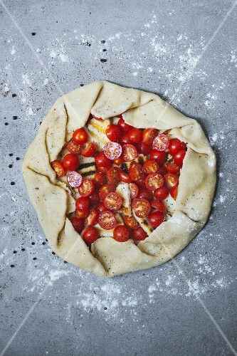 Unbaked tomato tart with ham (seen from above)