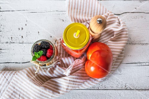 Cold tomato soup in a jar next to muesli with a jar of berries (seen from above)