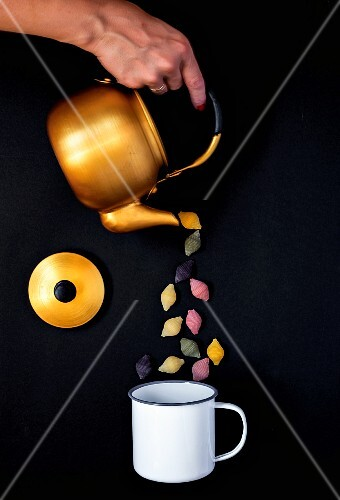 Shell pasta being poured from a teapot into an enamel mug