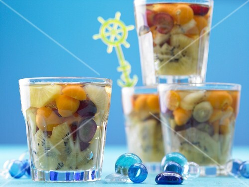 Fruit jelly with kiwi, grapes, physalis and pineapple in dessert glasses