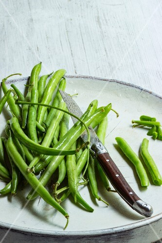 Fresh beans on a white plate with a knife being prepared