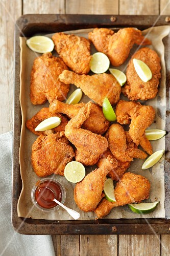 Breaded, fried chicken bits with limes and barbecue sauce on a baking tray