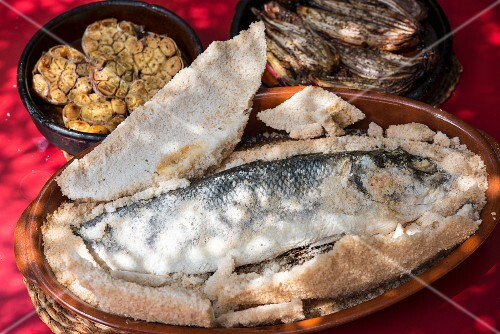 Sea bass in a salt crust with grilled garlic and onions