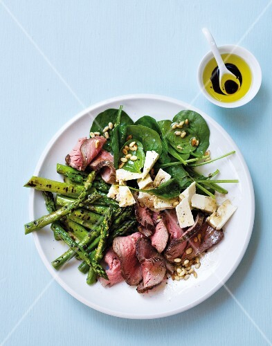 A salad with green asparagus, leaf spinach, beef fillet and feta cheese