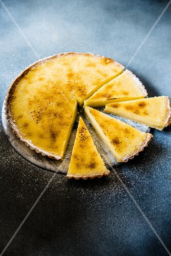 A sliced sugar-glazed lemon tart