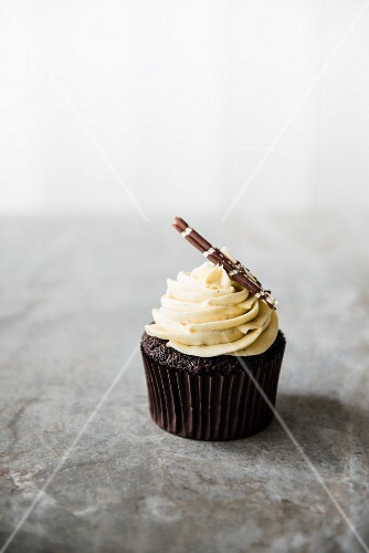 A chocolate cupcake with white chocolate cream on a marble surface.