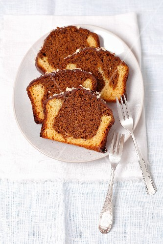 Several slices of marble cake with chocolate icing on a plate