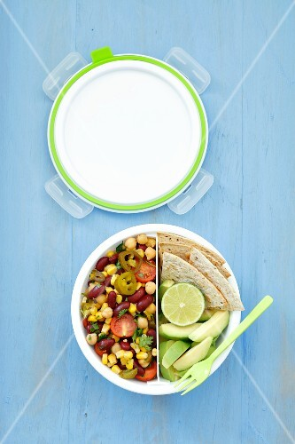A vegetarian lunchbox with a Mexican salad (red kidney beans, sweetcorn, tomatoes, chickpeas and jalapeno peppers), tortillas and avocado