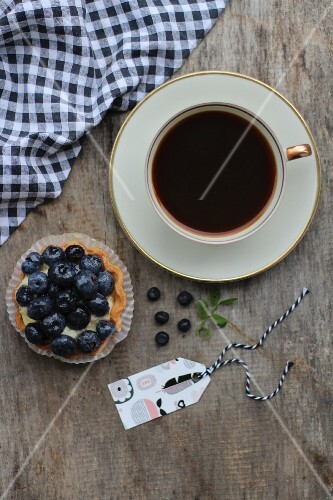 A cup of coffee and a blueberry tartlet