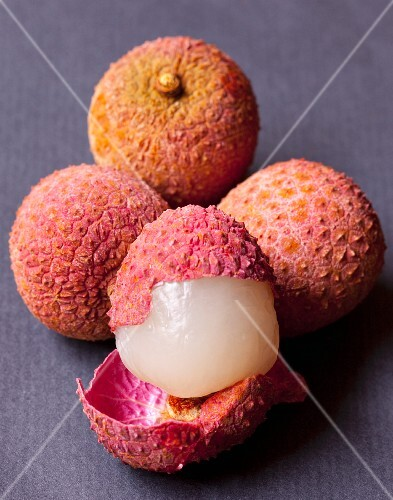 Several lychees, some whole and some cut open
