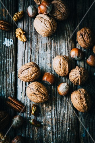 walnuts, hazelnuts and pistachios on a wooden surface