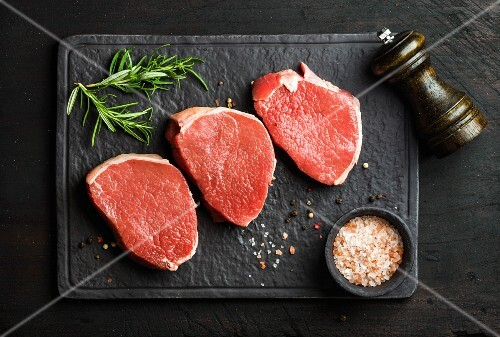 Raw beef Eye Round steaks with spices and rosemary on black slate stone board