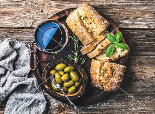 Glass of red wine, green mediterranean olives, freshly baked ciabatta bread in dark wooden plate