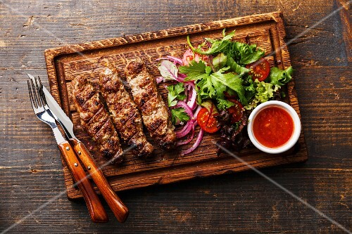 Grilled Lula kebab lamb with onions, salad and tomato spicy sauce Satsebeli on wooden board