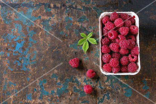 Paper market box of fresh raspberries with leaves over old wooden textured background