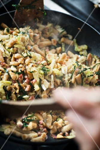 Spaetzle with savoy cabbage, quince and bacon in a pan