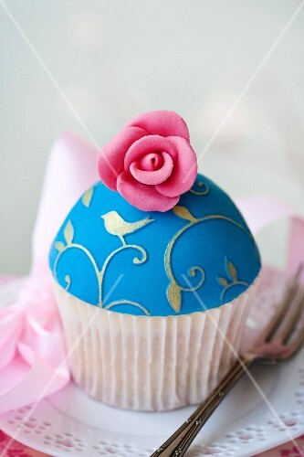 Cupcake decorated with gold embossing and a sugar rose