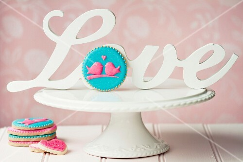 Cookies decorated with pink iced lovebirds, on a white cakestand with vintage love sign