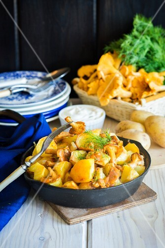 A frying pan with fried potatoes and chanterelle mushrooms