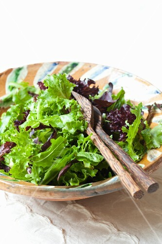 Mixed leaf salad in a salad bowl with cutlery