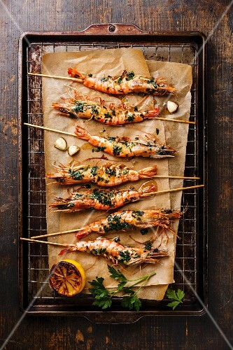 Grilled fried Tiger prawns shrimps on skewers with green sauce and lemon on metal grid baking sheet background
