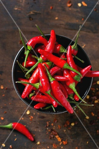 Red hot chilli peppers in a bowl and dried chilli flakes