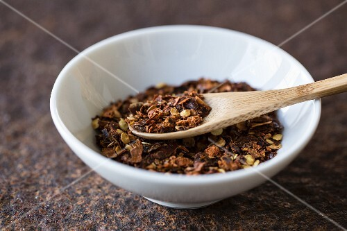 Chilli flakes with a wooden spoon in a bowl