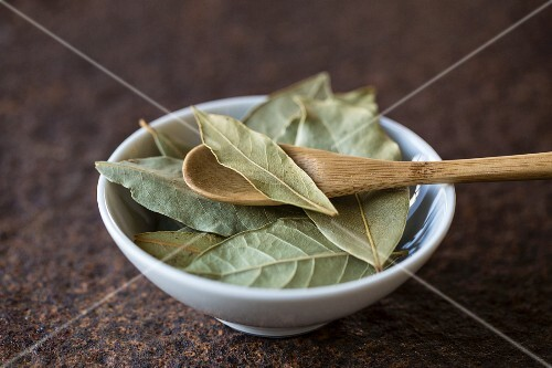 Dried bay leaves with a wooden spoon in a bowl